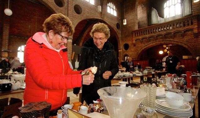 De vriendinnen Ger (links) en An uit Angeren snuffelen tussen de spullen tijdens de snuisterijmarkt van Volharding. (foto: Kirsten den Boef)