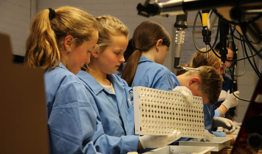 Leerlingen assembleren een luminaire aan de trainingslijn