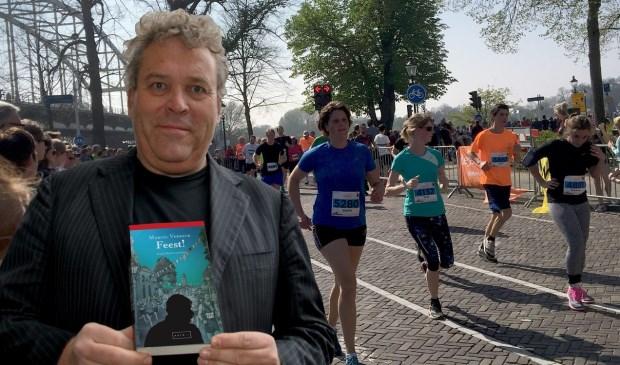 Marcel Verreck toont omslag Feest! tijdens een eerdere editie van de IJsselloop (fotomontage).