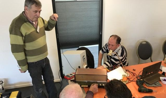 Vrijwillige techneuten aan het werk met een oude radio.