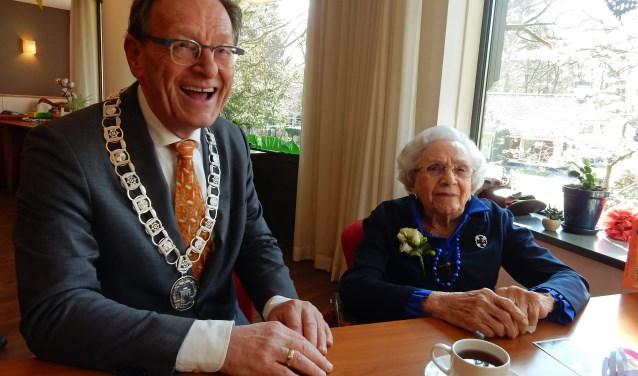 Mevrouw Van Os maakt grapjes met burgemeester Koos Janssen tijdens zijn bezoek op haar 100ste verjaardag. Hij prees haar jeugdige voorkomen. Foto: Asta Diepen Stöpler