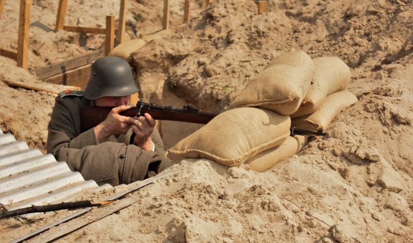Een Duitse scherpschutter zit klaar in zijn loopgraaf om met dodelijke precisie de vijand aan te vallen en uit te schakelen.