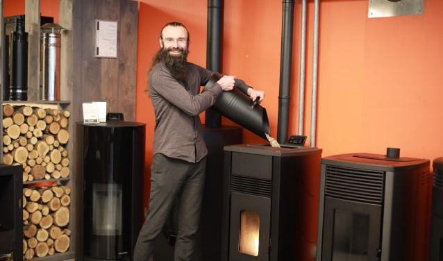 """Vincent demonstreert een pelletkachel. """"Bij pelletkachels heb je te maken met vuur, elektriciteit en een ventilator. We helpen onze klanten de kachel efficiënt te gebruiken."""" (foto: Feikje Breimer)"""