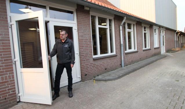 Trots bestuurslid Gidi van Riet bij de nieuwe kozijnen van het dorpscentrum.