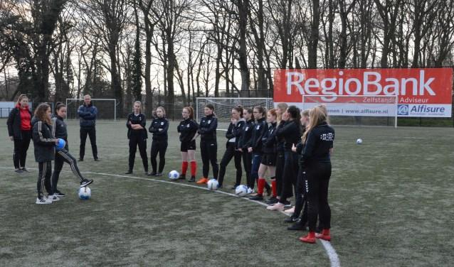 De Candia'66 speelsters luisteren aandachtig naar de lessen van twee Ajax-speelsters. (Foto: Theo Hoogendorp)
