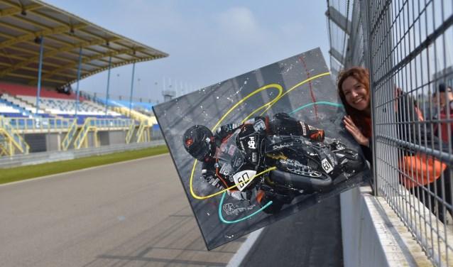 Marieke Brouwer met het schilderij van Rintje Ritsma op het circuit. Bieden op het schilderij kan tot zondag 12.00 uur.
