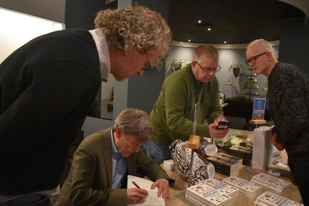 Uiteraard had Brusse de tijd om zijn boek te signeren. Hier met schrijver Frank Krake van het boek 'De Laatste Getuige'. Op de achtergrond John Reterink en de bezoeker uit Amsterdam. Foto: Jolien van Gaalen. Foto:  © Persgroep