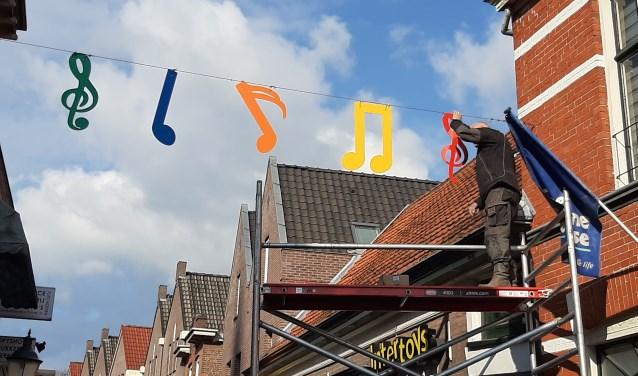 Ophangen van de muzieknoten in de Molenstraat.