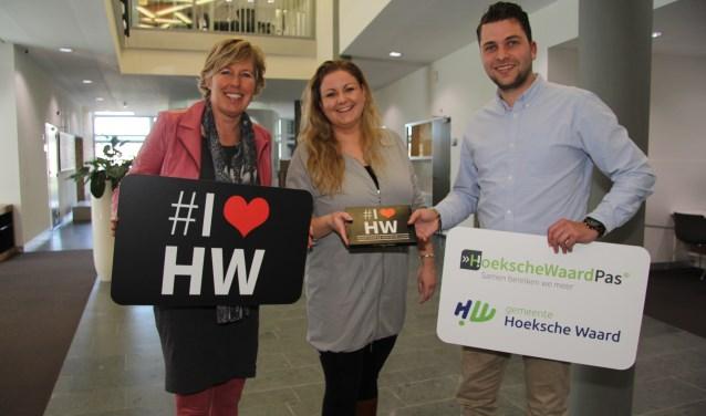 Margriet de Zoete namens de gemeente Hoeksche Waard, nieuwe inwoonster Sylvia van der Drift en Martin Herlaar van de HoekscheWaardPas.