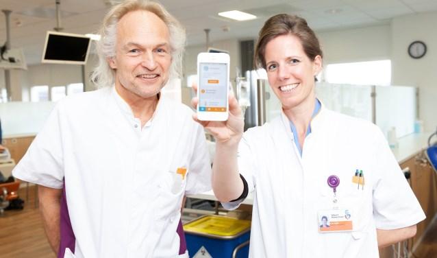 Internist-hematoloog Eva de Jongh en hematologieverpleegkundige Gerard Los met de app die patiënten extra houvast biedt in een toch al moeilijke tijd. (Foto: Frederike Roozen - Slieker)