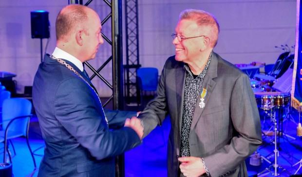 Burgemeester Vincent van Neerbos feliciteert Jan Sas met zijn onderscheiding. (Foto Caitlin Sas)
