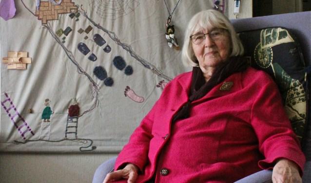 Jenny Schneider - Van Egten bij een wandkleed dat ze kreeg als cadeau en vol zit met symboliek. FOTO: Els van Stratum