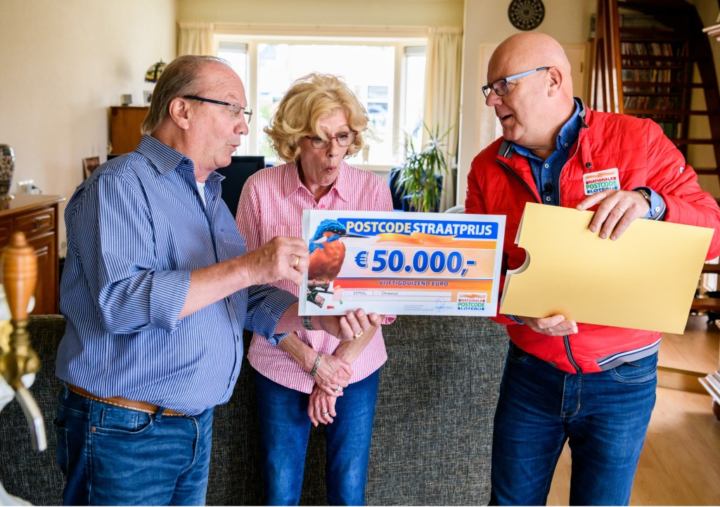 Frans en Jonieworden verrast door Postcode Loterij-ambassadeur Gaston Starreveld met de PostcodeStraatprijs-cheque. (Foto: Roy Beusker Fotografie)  © Persgroep