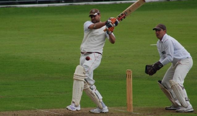 De batsman slaat de aangeworpen bal het veld in en voorkomt dat het wicket achter hem wordt geraakt.