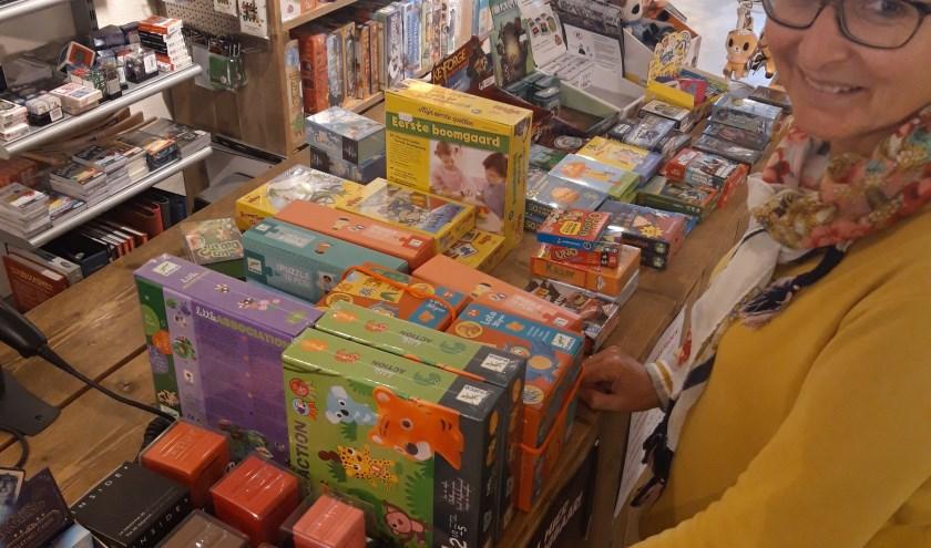 Tineke Knoester (Bibliotheek Rijn en Venen) met de grote stapel spellen bij spellen winkel Hoge Ogen in Alphen aan den Rijn.