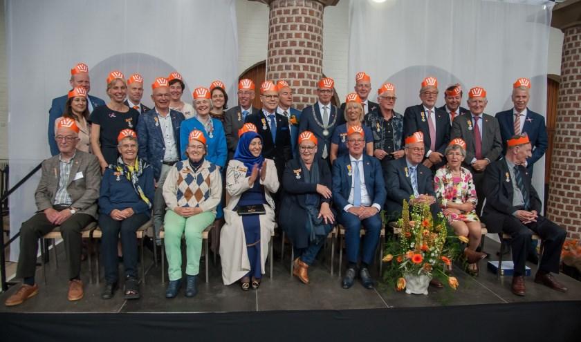 De onderscheidenen poseerden met burgemeester en wethouders in Oranjesfeer ter viering van het hoog bezoek op Koningsdag.