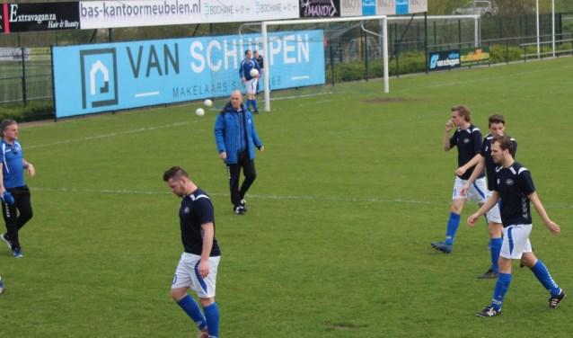 Ronald de Roos (blauw trainingsjack) dirigeert zijn spelers naar binnen voor een belangrijke wedstrijd op weg naar promotievoetbal. (Foto: Henk Jansen)