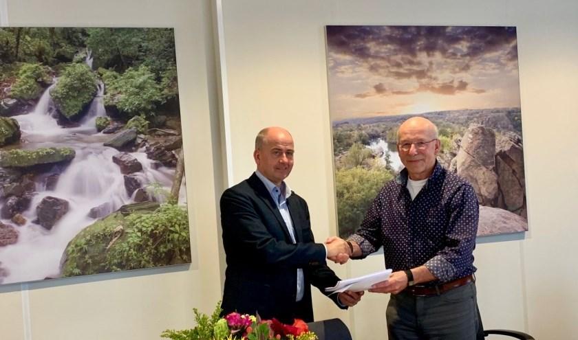 Theo Nelissen, voorzitter van Chapeau Woonkring Heusden, schudt Eric van den Einden, directeur-bestuurder van Woonveste, de hand.