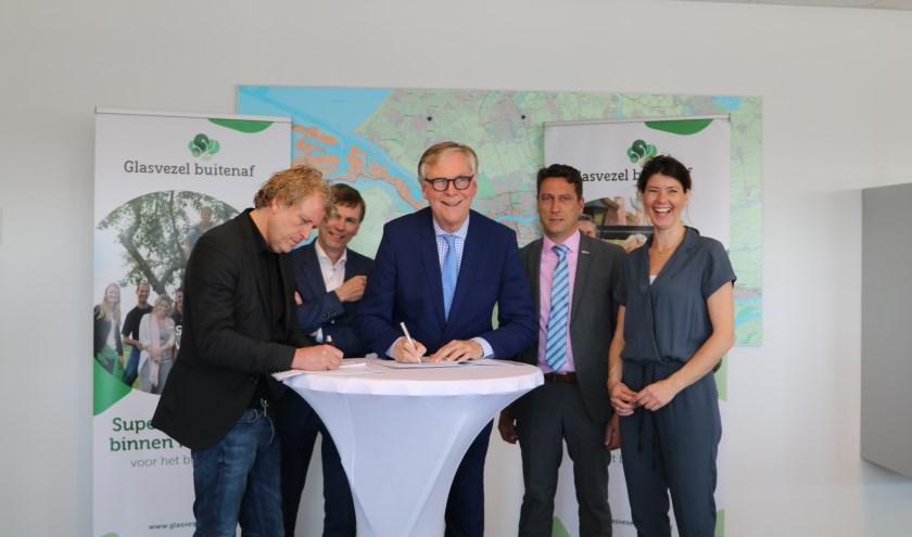Wethouders en directeur Glaszezel buitenaf maken afspraken voor glasvezel in buitengebieden van Voorne-Putten. Foto: PR