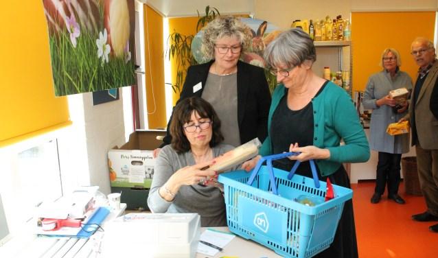 Edith Breure en Lineke Verkamman aan de kassa met een klant bij Albert Kleijntje Kats, (FOTO: LEON JANSSENS)