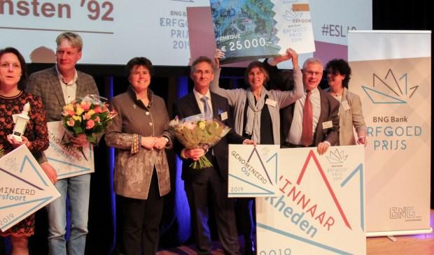 Een sportieve wethouder Van der Schoot (met bloemen, midden) met rechts de winnaars van de erfgoedprijs de gemeente Rheden.