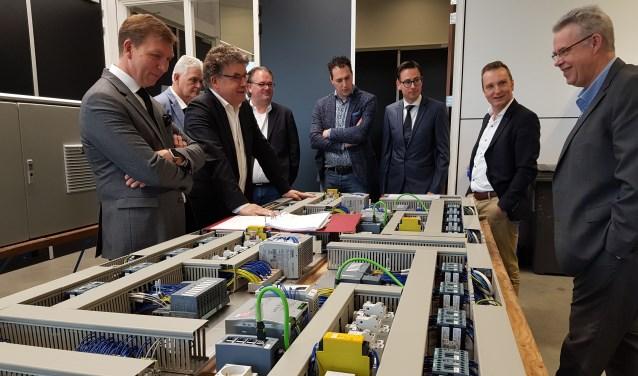 Rondleiding Techtron: links burgemeester Kats met naast hem Rob Stoffer en tegenover hem Ton van Voorthuijsen, directeur SanoRice. Deze besturingen maak Techtron voor Sanorice. (Foto's: Jan-Fotografie)