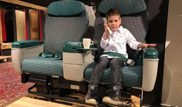 Zoontje Robin (4) vermaakt zich in één van de vliegtuigstoelen.