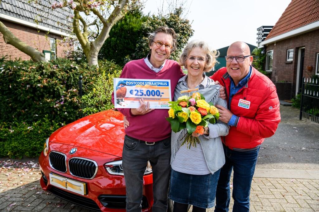 Rein en Truus worden verrast door Postcode Loterij-ambassadeur Gaston Starreveld met de PostcodeStraatprijs-cheque en de BMW. (Foto: Roy Beusker Fotografie)  © Persgroep