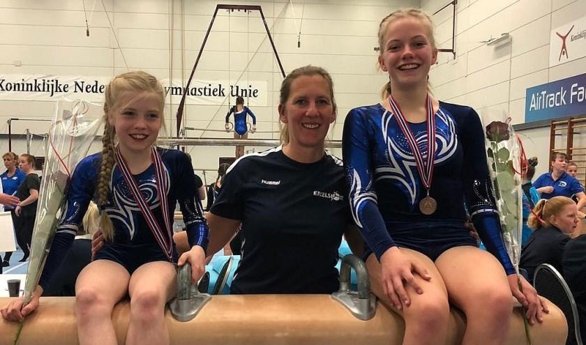 Trots tonen Tirsa en Isabel hun bronzen medaille met trainster Marjolein