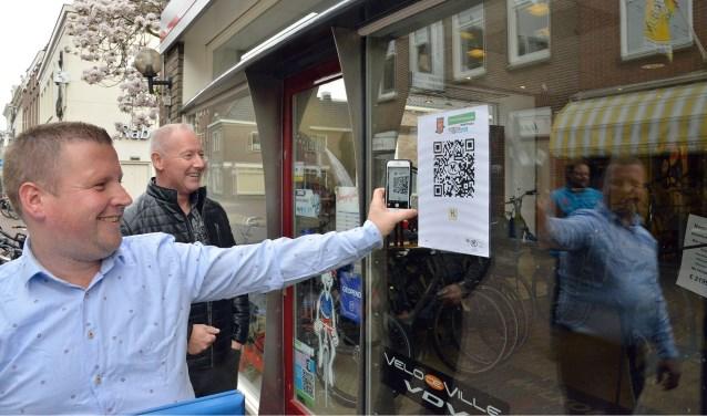 Terwijl Michel Verschoor toekijkt, laat Arjan van Dommelen zien hoe je met een mobieltje een QR-code scant. (Foto: Paul van den Dungen)