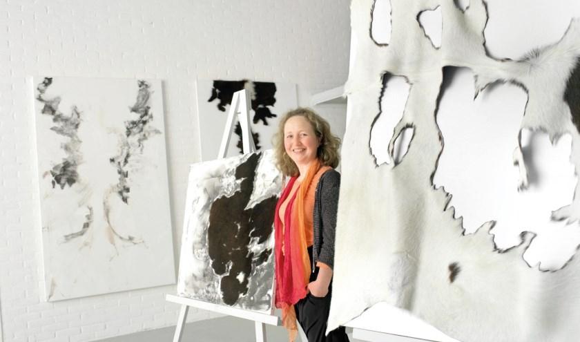 Sibyl Heijnen tussen haar werken. Foto onder: Koeien in de Hoenwaard. (foto's: Voerman Museum Hattem)