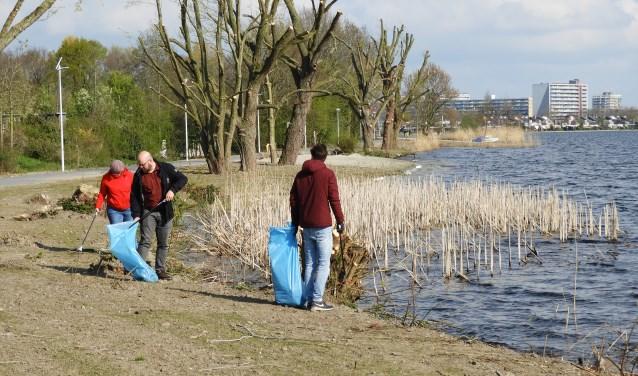 Vrijwilligers rapen vuilnis langs de plas. Aan het eind van de dag voert de gemeentewagen de blauwe vuilniszakken af.