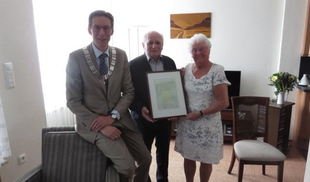 Uit handen van burgemeester Poppens mochten zij een gewaarmerkte kopie van de oorspronkelijke trouwacte ontvangen. FOTO: John Beringen