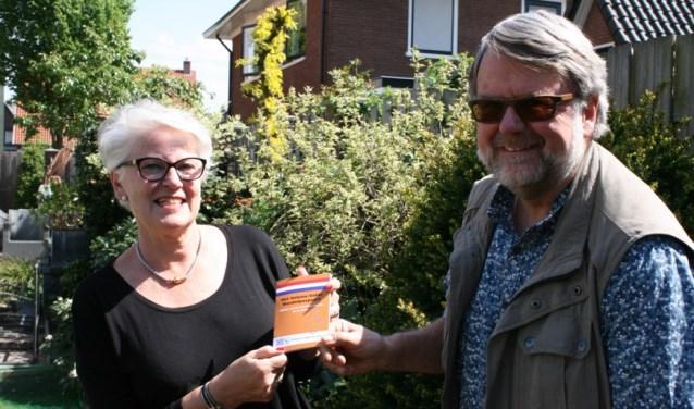 """Ruud Dijkman (SRVV) overhandigt het eerste Oranje Wandelpaspoort aan Lucia Broere: """"Zo'n paspoort met extra info is een extra aansporing om de Herinneringstochten te lopen!"""""""