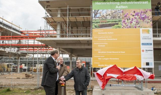 Bouwbord Industriestraat met Op de foto staan,  Ted Kok,  Martin Veldhuizen en Hans Beele.