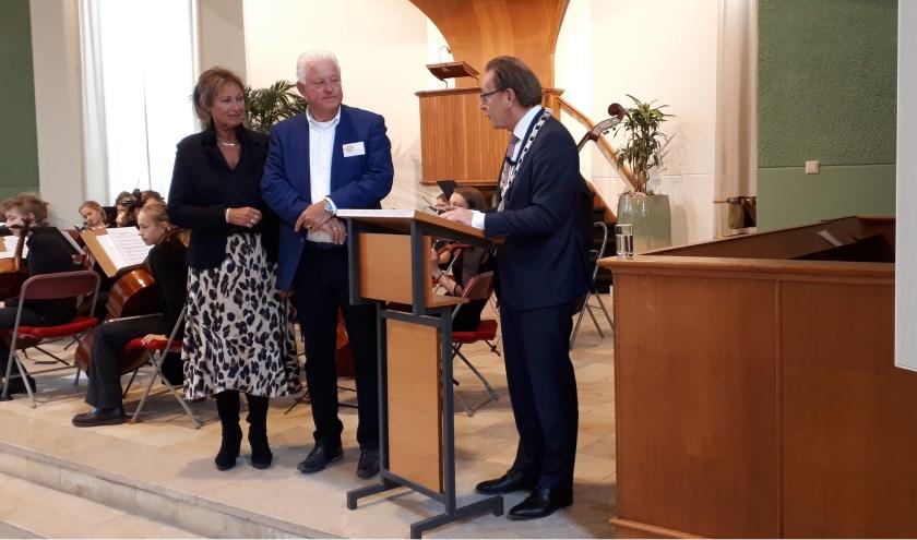 Burgemeester Koos Janssen spreekt een blij verraste Jelte Veenhoven toe in de volle Sionskerk. FOTO: Maarten Bos