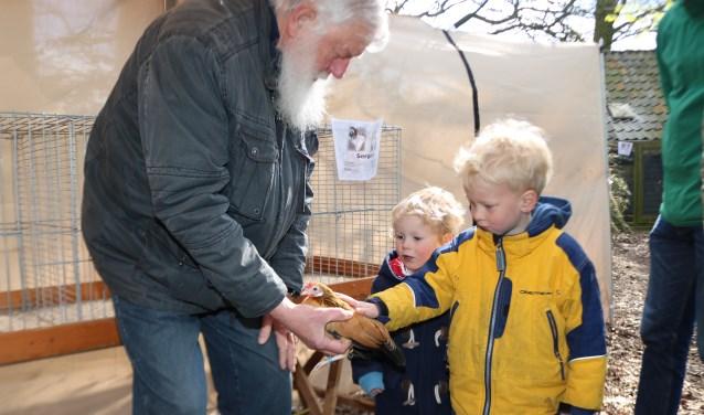 Jan ter Horst laat Laurend 93) en Herdrik (5) Sombekke  één van de kippen aaien. (Foto: Arjen Dieperink)