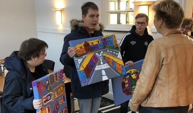 De kunstenaars van De Kubiek overhandigen de kleurrijke schilderijen aan directeur-bestuurder Erna Mobach van De Goede Woning. Eigen foto.