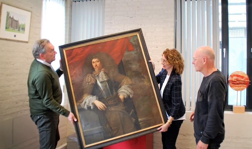 Onder toeziend oog van Hans Schoenmaker van Museum de Dorpsdokter halen de burgemeester en Han Smits dr. Fey van de wand.