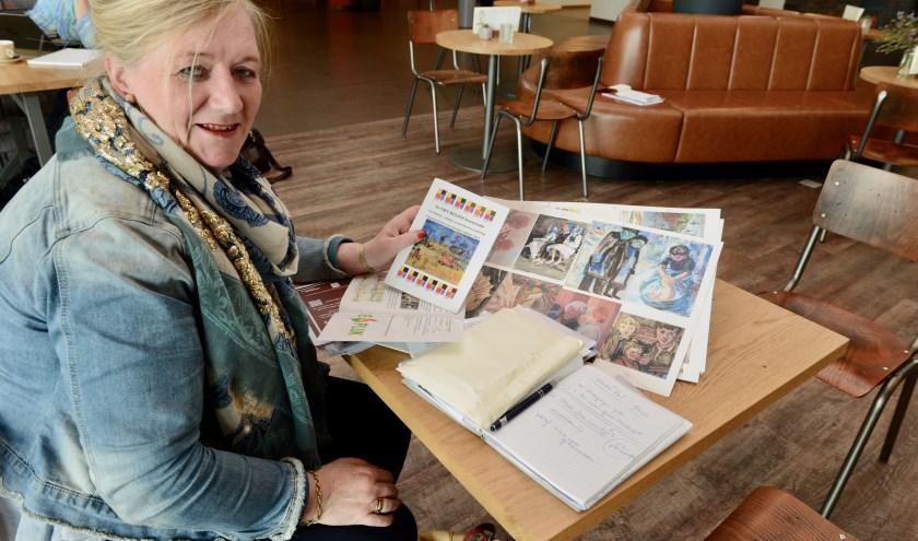 Voorzitter Joke van Vrouwerff in het Cultureelcentrum De Pluk bezig met de laatste voorbereidingen van 100 jaar Piet Mulder en controleert de drukproeven van de kunstkaarten.