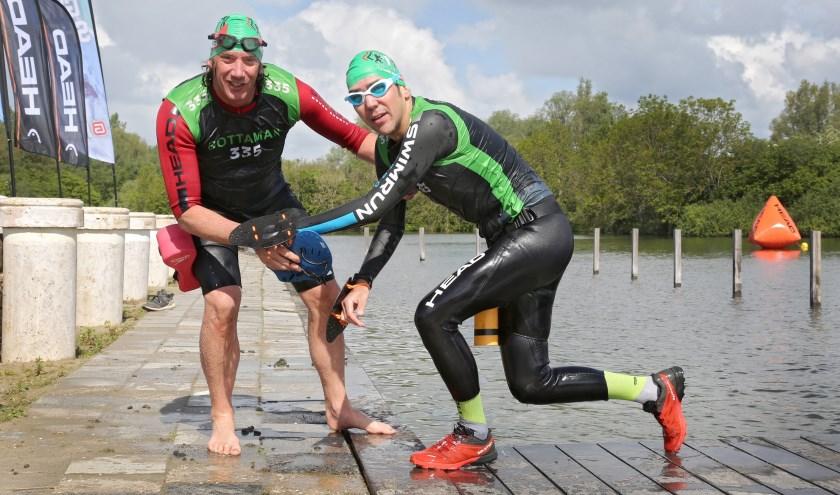 Erik Boer helpt Johan de Visser uit het water. Het gelegenheidsduo poseert voor de fotograaf. In de Swimrun 010 vormt Johan samen met Jacco van der Stigchel team WOEF. (Foto's: Rob Kamminga)