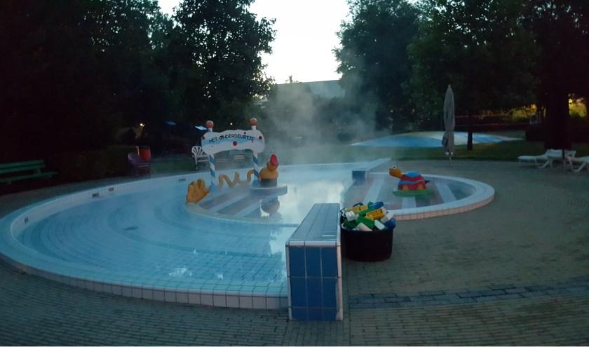 De damp slaat van het warme zwemwater af