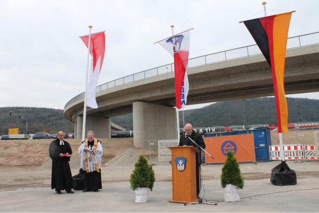 Burgemeester Jürgen Lippert van Gemünden aan het woord. Links wachten twee geestelijken op het moment dat ze de nieuwe brug kunnen inzegenen.