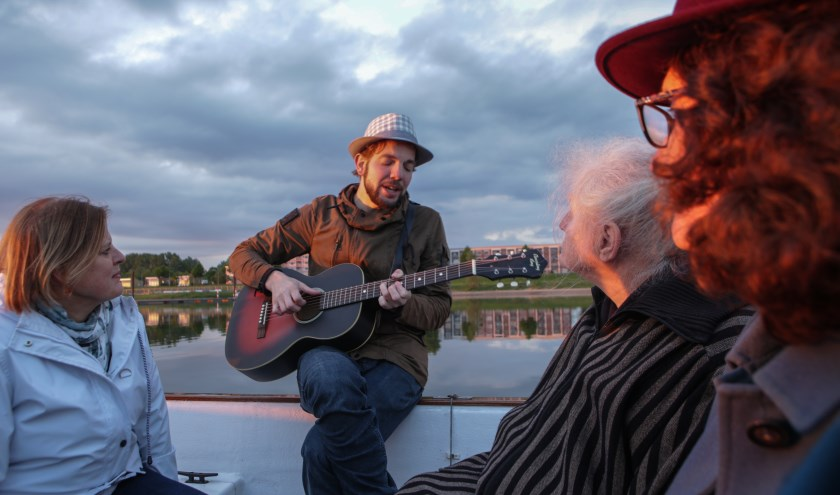 De Reisgenoot geeft een concert in een roeiboot op de IJssel