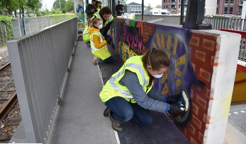 Een deel van de winnaars maakt het kleurrijke legale graffiti-kunstwerk op het station af. Foto: Jolien van Gaalen.