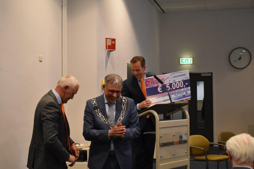 PinkRoccade Healthcare, samenwerkingspartner van de gemeente Wierden, heeft een cheque van 5000 euro overhandigd aan de Stichting Hulphond. Foto:  © Persgroep