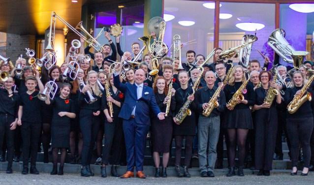 Muzikanten en oud-muzikanten van Unity, het opleidingsorkest van Eendracht, met hun dirigent Gerd Wensink.