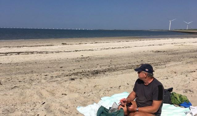 Het strandje van Ouwerkerk ligt er weer helemaal zomerproof bij. Afgelopen vrijdagmiddag zat een echte Ouwerkerker ervan te genieten. Hij komt op dit relatief onbekende strand veel vaker. FOTO: Gerrit van Loon