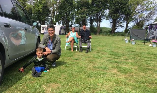 Lianne Verwest met zoontje Jona (3) op de camping bij de auto. Achteraan zitten Harry Kostense en zijn vrouw. FOTO: Gerrit van Loon