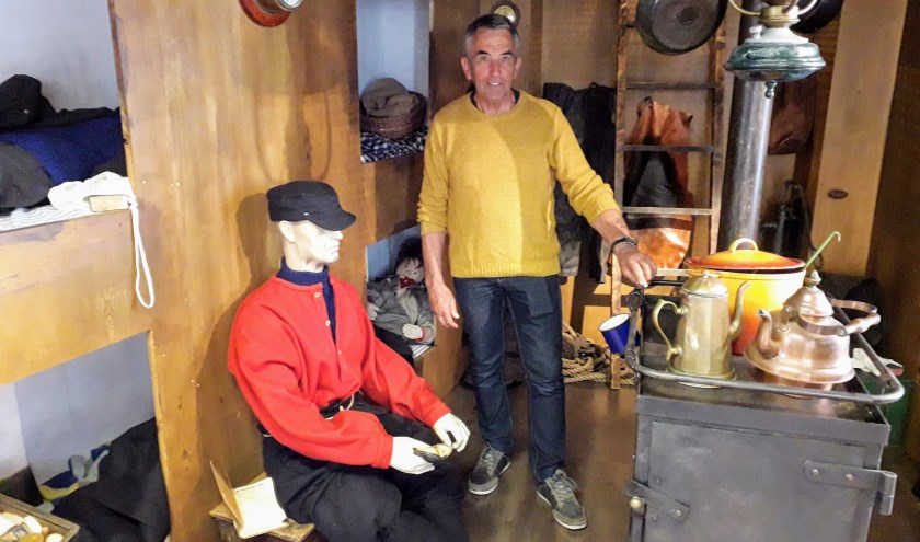 Jan van der Schee te midden van de tentoonstelling 'geen zee te ver' in de Oudheidkamer over het visserijverleden van Pernis. Foto: Jacco van Oldenburg